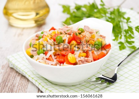 colorful salad with corn, green peas, rice, red pepper and tuna, close-up, horizontal