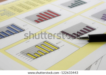 Colorful sales charts with pen.