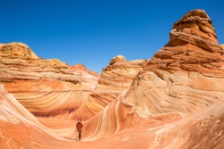 Colorful sandstone rock behind hiker in red and brown as he walks through The Wave in northern Arizona. Striated sandstone creates many curves and interesting lines.