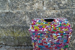 Colorful scarp of paper to stick around the bin or trash that obvious  is in front of the old block concrete wall at the public park for peple to leave the garbage in place.