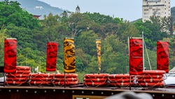 Colorful scene with red lifebuoys and traditional flags with dragons on wooden berth against green trees on blurred background in Shum Wan Pier, Hong Kong, China