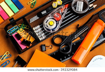 colorful school and office supplies on an orange background stock photo