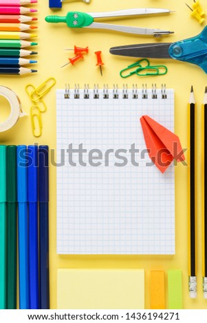 Colorful school stationery and supplies collection on yellow background. Organized desktop space. Copy space.