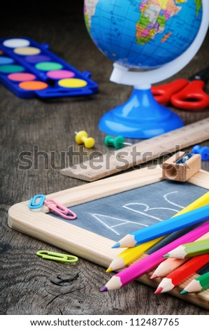 Colorful school supplies on old wooden desk