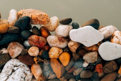 Colorful sea pebbles close-up. Background texture, sea stones in the water.