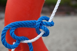 Colorful sea ropes in blue and white on the background of an orange lifebuoy. Selective focus