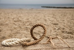 Colorful sea ropes lie on a wooden deck, covered with sand . Nearby lies a picturesque snag. Selective focus