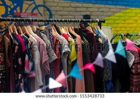 Colorful secondhand clothes on hangers at local market on the street Stockfoto ©