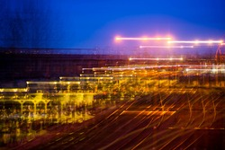 Colorful semi-abstract night city landscape. The photo is done with long exposure and is consists  of a several approximate pictures. Concept of speed, business, metropolis, fast way of living