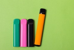 Colorful set disposable electronic cigarette pod on a blue background. alternative to modern smoking, vaping and nicotine. tobacco substitution black in rose background