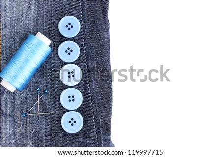 Colorful sewing buttons with thread on jeans isolated on white