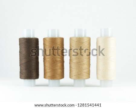 Colorful sewing threads on white background with space for text, sewing accessories isolated, shadow of brown and fulvous.