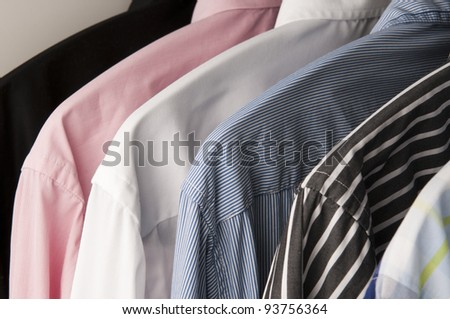 Colorful shirts that are hanging in a wardrobe.