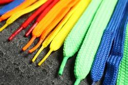 Colorful shoelaces on grey background, closeup. Stylish accessory