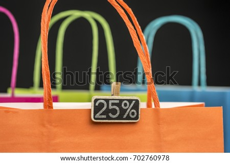 Colorful shopping bags with wooden peg tag attached writing 25 percernt discount