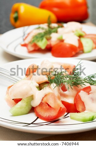 Colorful shrimp salad with tomatoes, cucumber and some dill for garnish with bell peppers in the background