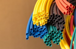 Colorful shrink tube on brown background, close-up