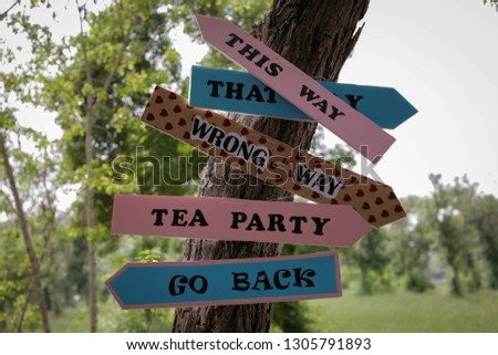 Colorful signs on tree in park pointing direction to tea party, go back, wrong way, this way #1305791893