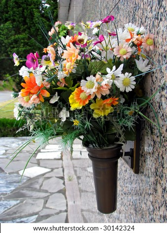 colorful silk flower vases in summer cemetery