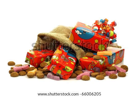 "colorful ""Sinterklaas""presents in a burlap sack with some ginger nuts and candy on a white background"
