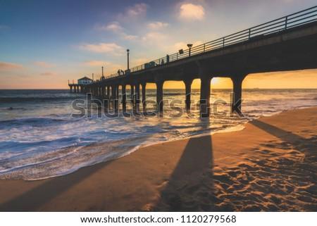 Colorful sky and clouds over Manhattan Beach Pier at sunset with long shadows cast on the beach, Manhattan Beach, California #1120279568