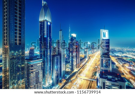 Colorful skyline of a big modern city with illuminated skyscrapers and highways. Aerial view over downtown Dubai, UAE. Travel and architectural background. #1156739914