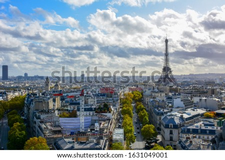 Colorful skyline of Paris, France, with the Eiffel Tower, the dome of Les Invalides, Montparnasse tower and famous Parisian boulevards on a sunny autumn day, captured from the top of Arch de Triomphe