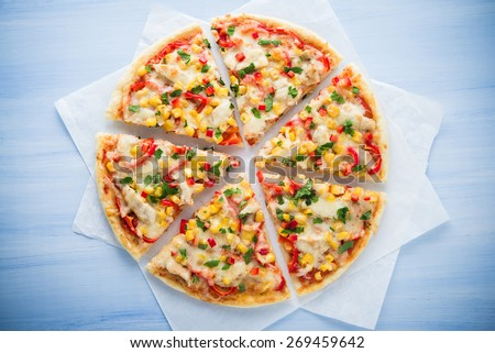 Colorful sliced pizza with mozzarella cheese, chicken, sweet corn, sweet pepper and parsley close up top view. Italian cuisine.