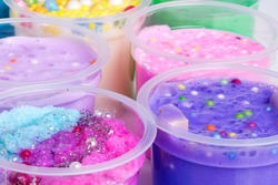 Colorful slimes inside plastic boxes. Set of kids gunk toy, close up view.