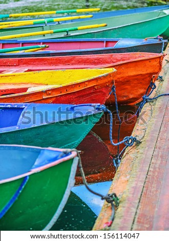 Colorful small boats parked to wooden pier.