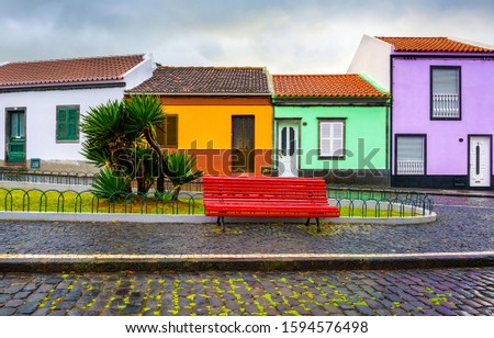 Colorful small street houses view. Red bench at colorful houses street. Colorful small houses red bench