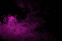 Colorful smoke close-up on a black background. Blurred pink cloud of smoke.