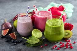 Colorful smoothie, healthy detox vitamin diet or vegan food concept, fresh vitamins, breakfast drink with spinach, pomegranate, figs and blueberries