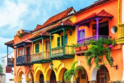 Colorful spanish colonial buildings with wooden balconies at Plaza de los Coches inside the walled city of Cartagena de Indias, Colombia. UNESCO world heritage site.