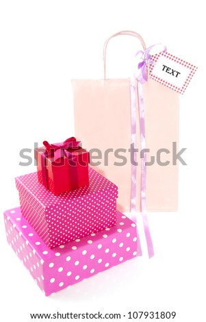 Colorful speckled giftboxes with pink shoppingbag isolated over white
