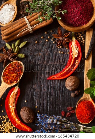 Colorful spices and herbs frame on a wooden background.