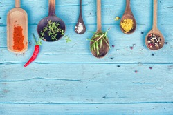 Colorful Spices and herbs on rustic spoons over blue wooden background