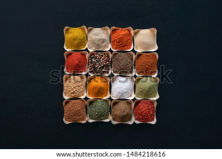Colorful spices background. Variety of spices, herbs and seasoning in small bowls in the center of a black background. Above view with condiments.