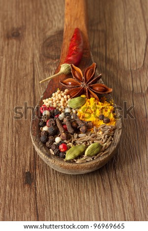 Colorful spices in a wooden spoon on the old table.
