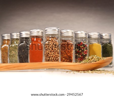 Colorful spices in bottles with wooden spoon