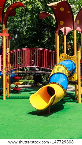 Colorful Spiral Tube Slide with Green Elastic Rubber Floor for Children in the Park