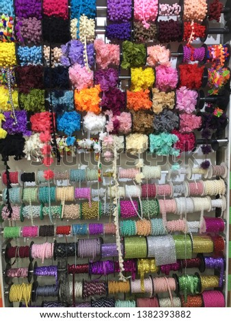 Colorful spools at diy store, pom poms, lace #1382393882