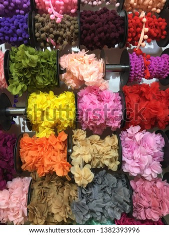Colorful spools at diy store, pom poms, lace #1382393996