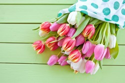 Colorful spring flowers on green wooden boards
