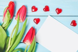 Colorful spring tulip flowers with blank photo and decorative red hearts on light blue wooden background as greeting card. Mothersday, love or spring concept.