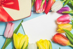 Colorful spring tulip flowers with decorative giftbox and blank photo on light blue wooden background as greeting card. Mothersday or spring concept.