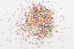 Colorful sprinkles spilled from a jar on white table