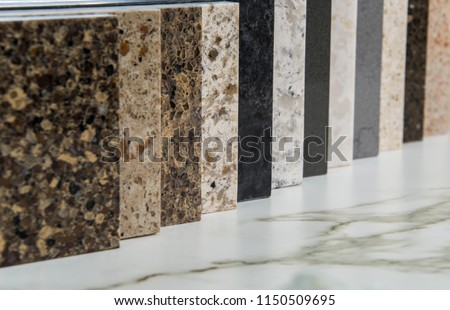 Colorful square color samples of kitchen granite, marble and quartz countertop, made of natural stone in line on white carrara marble slab with gray/brown grains