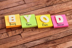 Colorful square papers with wooden white letters for the acronym word BYOD (Bring Your Own Device)