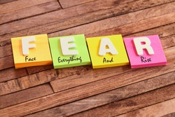 Colorful square papers with wooden white letters for the acronym word FEAR means Face Everything And Rise